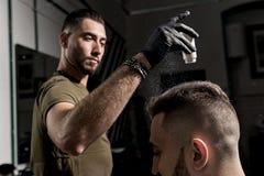 Den stiliga barberaren fixar utforma av den brutala unga skäggiga mannen med en torr styler på en frisersalong arkivfoto