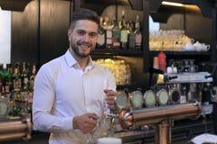 Den stiliga bartendern ?r le och fylla ett exponeringsglas med ?l, medan st? p? st?ngr?knaren i bar royaltyfria bilder