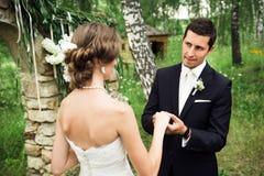 Den stiliga brudgummen fixar en vigselring royaltyfri fotografi