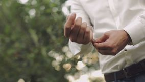 Den stiliga brudgummen fixar hans skjorta Bröllopmorgon långsam rörelse Få skott lager videofilmer