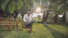 Den stiliga brudgummen fixar hans skosnöre på skor Bröllopmorgon i trädgården långsam rörelse lager videofilmer