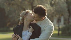Den stiliga brudgummen kommer till bruden bak henne och sätter stock video