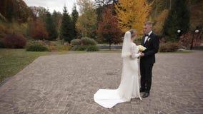 Den stiliga brudgummen och charmabruden spenderar si, e tillsammans, efter gifta sig ceremoni i har parkerat lager videofilmer