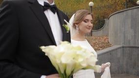 Den stiliga brudgummen och charmabruden spenderar si, e tillsammans, efter gifta sig ceremoni i har parkerat stock video