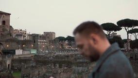 Den stiliga brunettmannen med ett skägganseende på fördärvar i Rome, Italien som ser översikten i hans händer långsam rörelse lager videofilmer