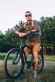 Den stiliga cyklisten för den unga mannen i solglasögon med cykeln i sommar parkerar under resande avkoppling för solnedgångsemes royaltyfria foton