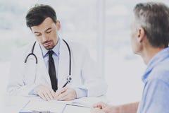 Den stiliga doktorn med stetoskopet skriver anmärkningar Royaltyfri Foto
