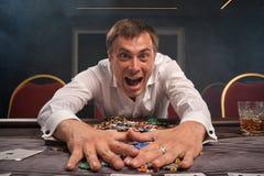 Den stiliga emotionella mannen spelar poker som sitter på tabellen i kasino royaltyfri foto