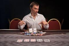 Den stiliga emotionella mannen spelar poker som sitter på tabellen i kasino royaltyfria foton