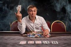 Den stiliga emotionella mannen spelar poker som sitter på tabellen i kasino fotografering för bildbyråer