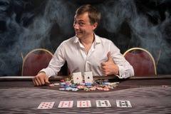 Den stiliga emotionella mannen spelar poker som sitter på tabellen i kasino arkivfoto