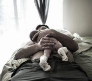 Den stiliga fadern ligger på sängen, och innehavet med omsorg hans söta nyfött behandla som ett barn sonen Royaltyfri Fotografi