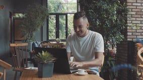 Den stiliga galna emotionella unga lyckliga manliga grabbaffärsmannen visar framgång i mysigt kafé Manarbete på compter som in le stock video