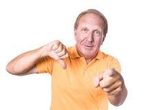 Den stiliga gamala mannen med den orange polo-skjortan visar tummen upp och pointin Royaltyfria Bilder