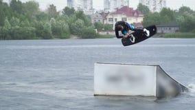 Den stiliga grabben i en wetsuit rider en wakeboard på floden lager videofilmer