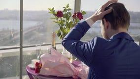 Den stiliga grabben i ett stilfullt omslag som sitter med hans baksida till kameran på en tabell i ett kafé eller en restaurang o lager videofilmer