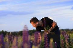Den stiliga grabben samlar blommor i fältet Arkivbilder