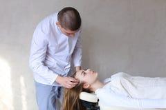 Den stiliga grabbmassageterapeuten som gör den head massagen för flicka, clien arkivbilder