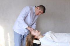 Den stiliga grabbmassageterapeuten som gör den head massagen för flicka, clien arkivfoton