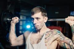Den stiliga idrotts- mannen utbildar skuldror som lyfter skivstångsammanträde på bänken i idrottshallen arkivbilder