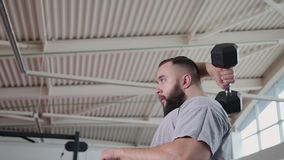 Den stiliga idrotts- mannen utbildar triceps på kvartersimulatorn i idrottshallen lager videofilmer