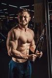 Den stiliga idrotts- mannen utför övningen för triceps i idrottshallen Arkivfoto