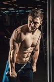 Den stiliga idrotts- mannen utför övningen för triceps i idrottshallen Royaltyfri Fotografi