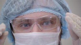 Den stiliga kirurgen i maskering ser kameran som står i ett modernt fungeringsrum, slutet upp, patienten i klinik arkivfilmer
