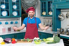 Den stiliga kocken inviterar till att laga mat Förberedda grönsaker för man för att laga mat med förälskelse Grabbvälkomnanden ti Arkivbild