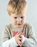 Den stiliga koncentrerade pojken korsar hans armar. Royaltyfri Fotografi