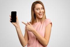 Den stiliga kvinnan med pekfingret visar den tomma telefonskärmen var du kan förlägga din annons Den positiva unga flickan ler sn arkivbild