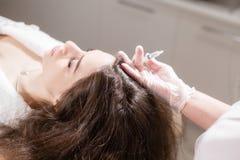 Den stiliga kvinnan mottar en injektion i huvudet Tillvägagångssättet gör doktorn i vita handskar Begreppet av mesotherapy Royaltyfria Bilder