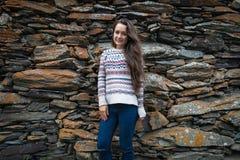 Den stiliga kvinnan står på bakgrund av stenar arkivfoto