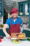 Den stiliga le kocken med den tatuerade handen rymmer skärbrädan med paprika och kål Kocken sätter paprika in i den gula plattan royaltyfria foton