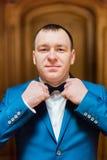 Den stiliga le mannen i blått passar fixin hans fluga i rik träinre Fotografering för Bildbyråer