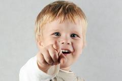 Den stiliga lyckliga blonda pojken pekar framåtriktat vid finge Arkivbilder