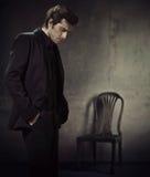 Den stiliga manen i en affär passar på en mörkerbakgrund fotografering för bildbyråer