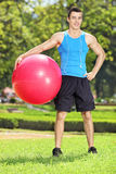 Den stiliga manliga idrottsman nen som in poserar, parkerar med pilatesbollen Royaltyfria Foton