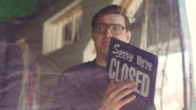 Den stiliga manliga kaféarbetaren i förkläde ändrar dörrskylten från `, ja som vi är öppen ` till ledsen ` oss är stängd `, Slut  stock video