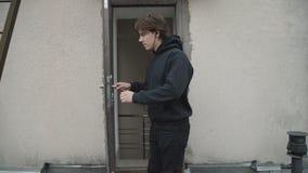 Den stiliga mannen öppnar dörren och kommer ut på taket 4K arkivfilmer