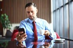 Den stiliga mannen arbetar i kafé, dricker koppen kaffe, ler och ser den smarta telefonen Royaltyfri Bild