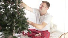 Den stiliga mannen dekorerar julgranen stock video
