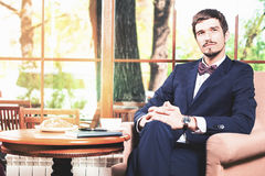Den stiliga mannen har en fransk frukost på kaférestaurangen Royaltyfria Foton