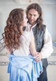 Den stiliga mannen i medeltida dräkt klär av den härliga kvinnan royaltyfria bilder