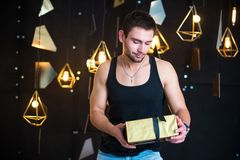 Den stiliga mannen i svart ärmlös tröja rymmer en gåva i hennes händer, öppnar en gåva, gåva fotografering för bildbyråer