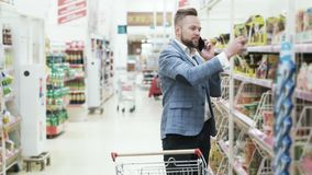 Den stiliga mannen i den vita skjortan talar på telefonen och köpande livsmedel i supermarket stock video