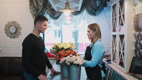 Den stiliga mannen kommer till en blomsterhandel och frågar blomsterhandlaren om blommor stock video