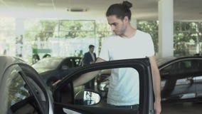 Den stiliga mannen kontrollerar bilen i bilåterförsäljare stock video