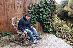 Den stiliga mannen kopplar av i tappninggungstol med telefonen i trädgård Royaltyfria Bilder
