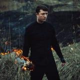 Den stiliga mannen med en fackla i hans handuppsättningar avfyrar till gräset in arkivfoto